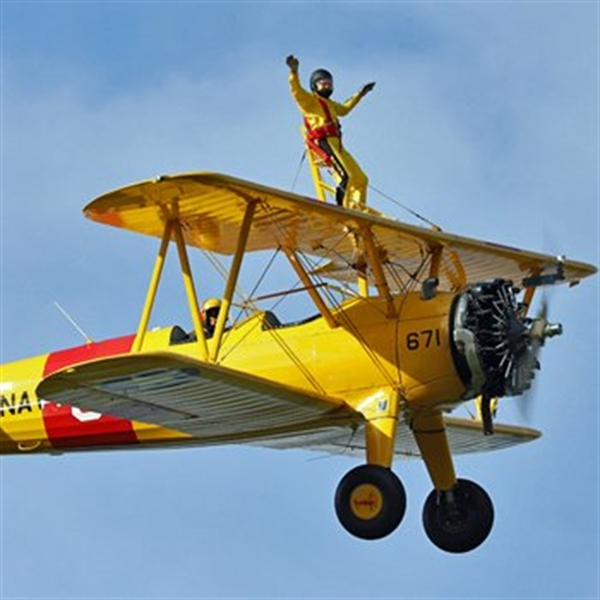 man wingwalking with thumbs up