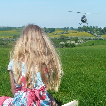 girl on hill with views of helicopter